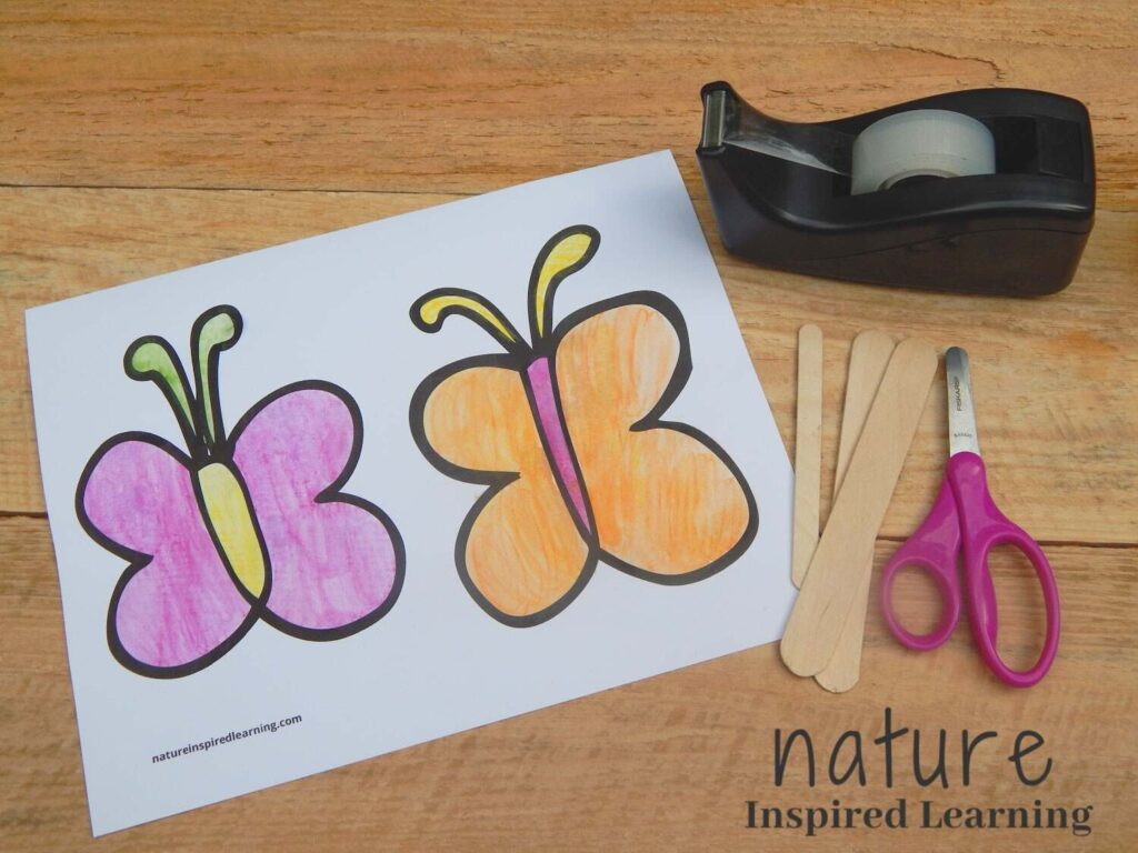 painted butterfly template printable on a wooden surface with one popsicle stick, two wooden craft sticks, pink safety scissors, and a tape dispenser with clear tape text nature inspired learning bottom corner