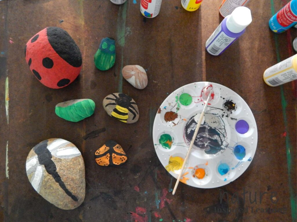 rock painting insects, dragonfly, butterfly, caterpillar, bee, moth, click beetle, lady beetle, on a painting board with a circular paint tray with used acrylic paints and a small paint brush place on it with acrylic paint bottles in background