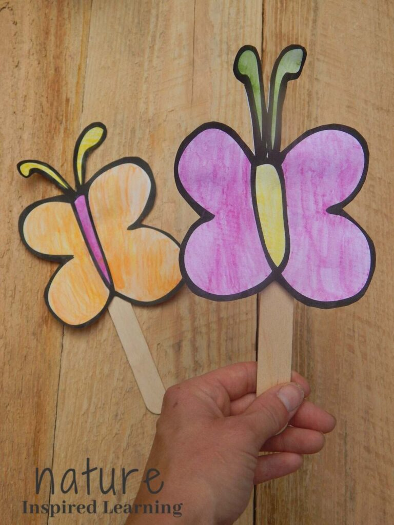 hand holding a paper butterfly craft pink, yellow, and green watercolor paint cut out and taped to a wooden craft stick.  A second orange, pink, and yellow butterfly paper craft on the wooden table below text nature inspired learning bottom corner