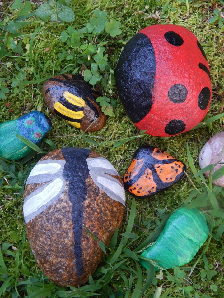 collection of rock painting insects outside in garden ladybug painted rock, dragonfly rock art, caterpillar rock art, butterfly rock painting, beetle rock art, bee rock painting, and moth rock art