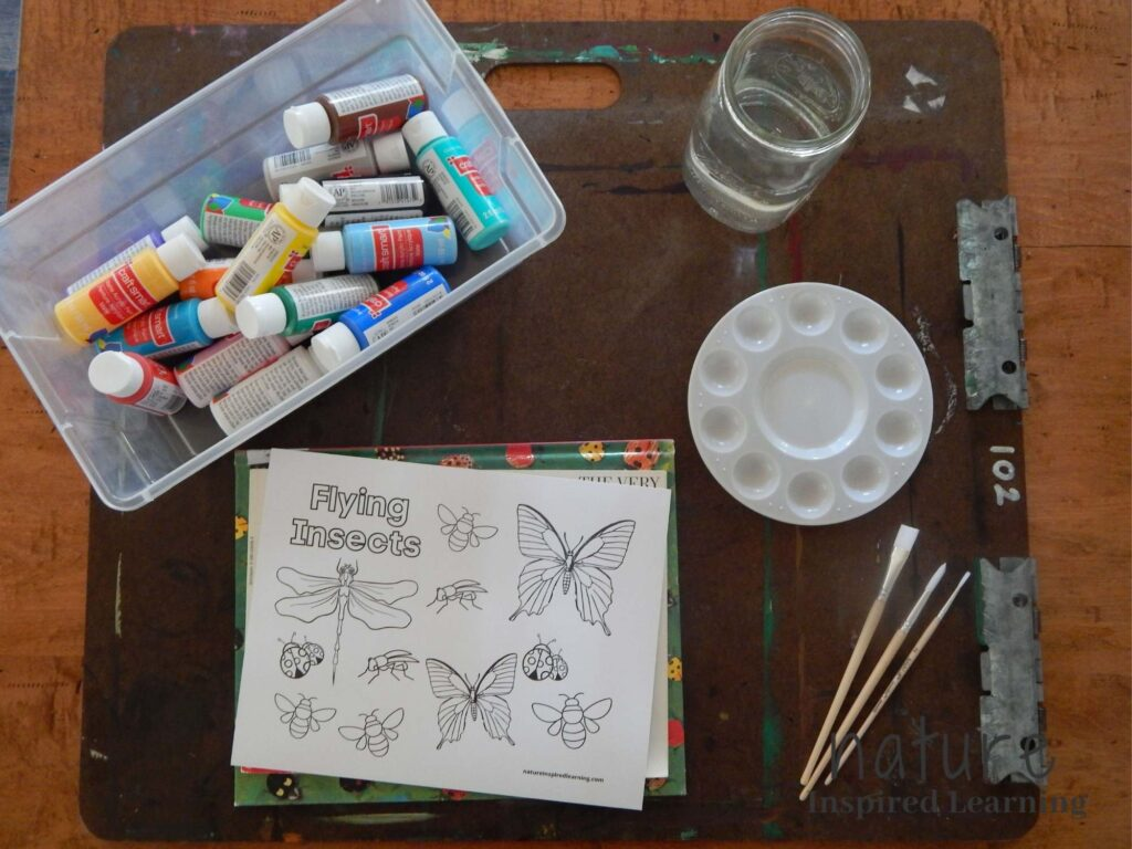 clear plastic tote with acrylic paints in various colors, glass jar with water, circular painting tray, three wooden paint brushes, flying insects printable on top of bug children's books, all on a art board on a wooden table