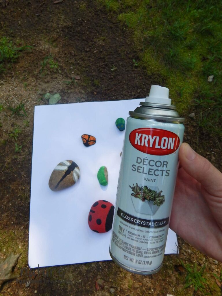 hand holding Krylon decor selects gloss crystal clear spray paint can over insect painted rocks on recycled paper outside in shade