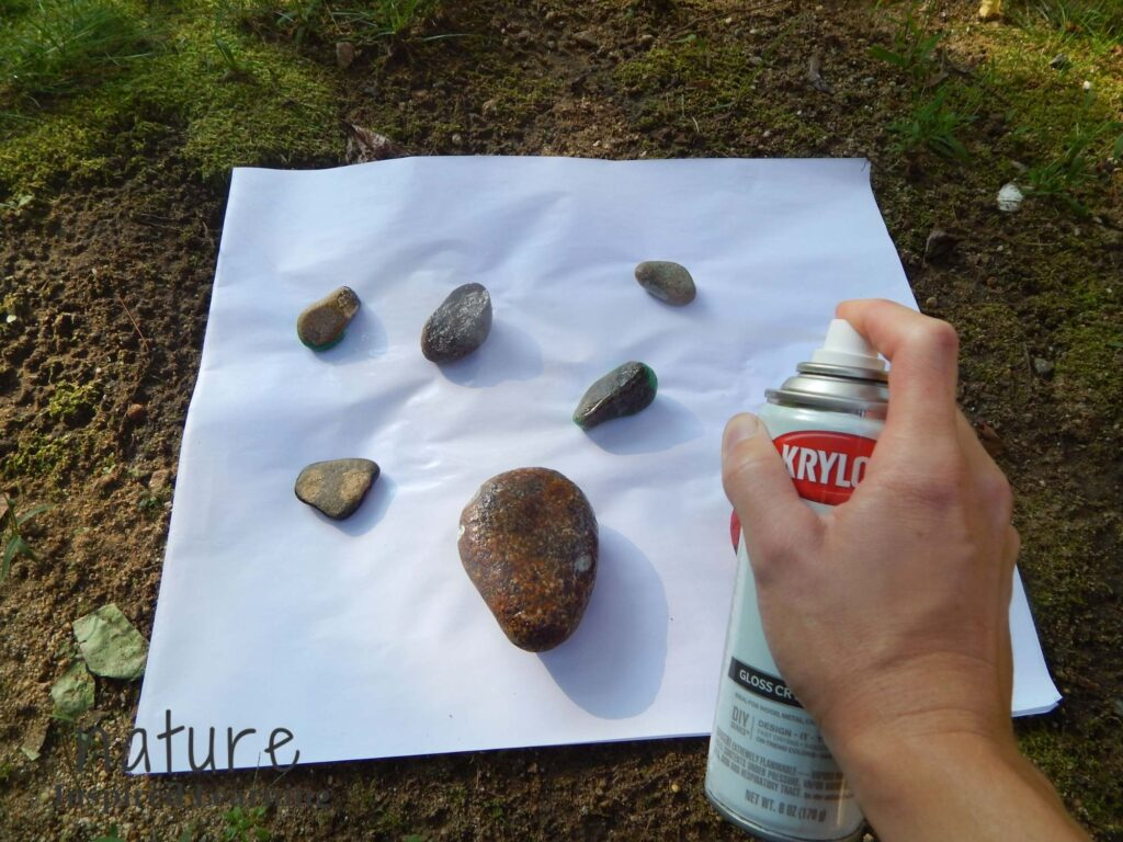 hand holding can of krylon gloss craft spray paint over a white recycle paper with over turned insect painted rocks outside in the shade