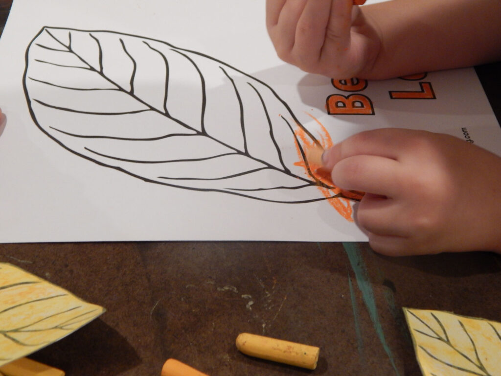 toddler's hand coloring a fall leaf printable holding an orange oil pastel yellow pastel on the wooden table