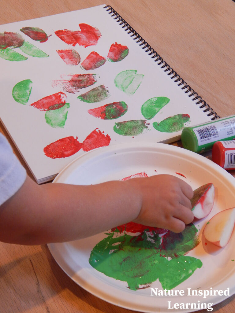 toddler making apple process art painting with apples red and green acrylic paint apple prints on blank paper spiral bound pad with paint on a paper plate with apple slices red and green paint containers