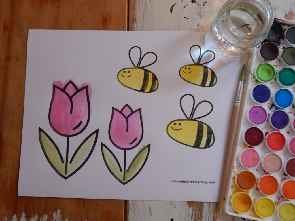 honey bee coloring sheet printed off an painted in yellow and black happy bees, two pink flowers with watercolor painting supplies on wooden table