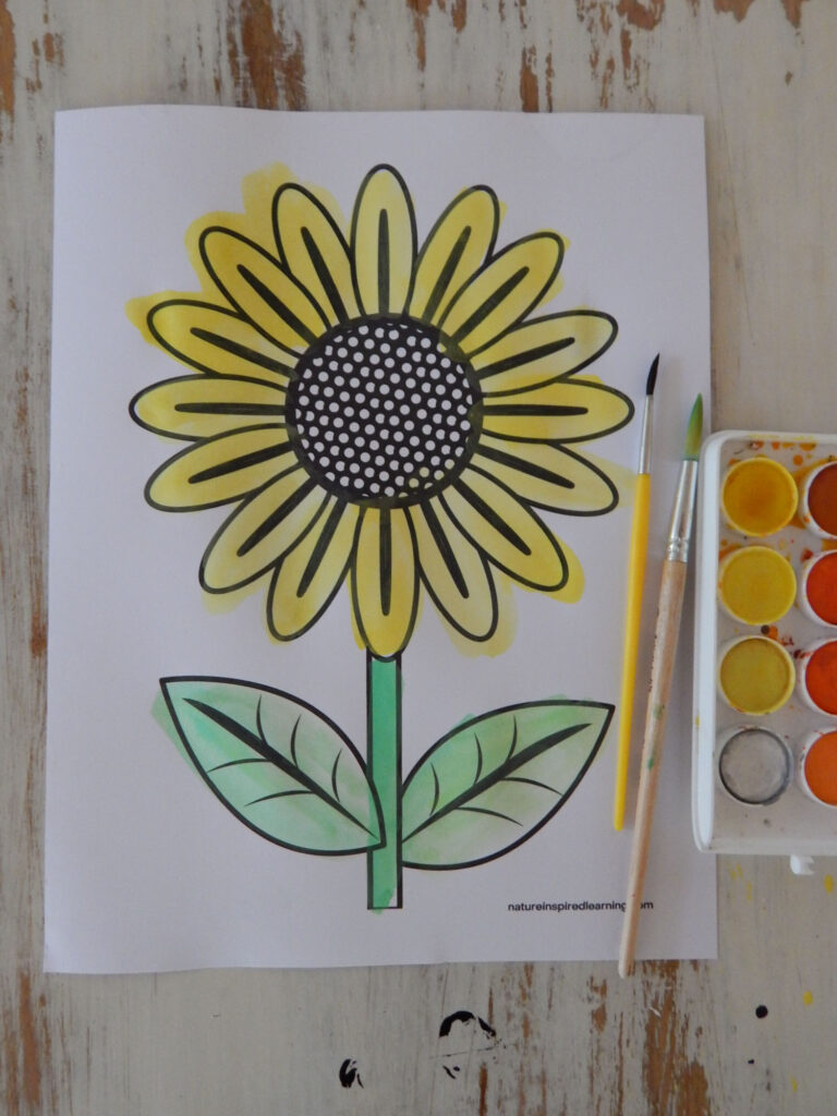big sunflower coloring page with bright yellow painted petals with painted green stem and leaves two paint brushes with paint set to the side of the printable