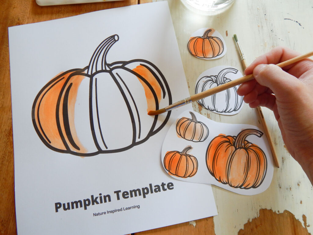 hand holding a paint brush painting orange on a printed off pumpkin template coloring sheet with little pumpkins cut out of paper also painted orange extra paint brush on table with glass of water