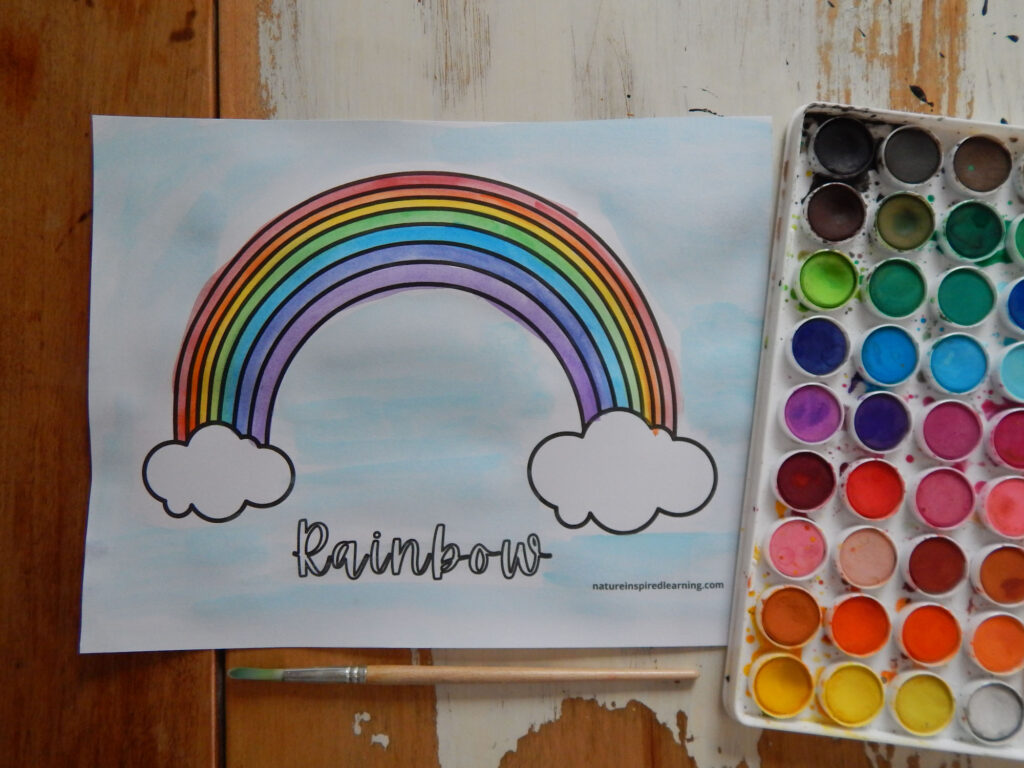 rainbow with white clouds coloring page with word rainbow written in cursive painted in using watercolor paints in roy g biv to create a rainbow with blue painted sky watercolor set and paint brush on table with coloring sheet