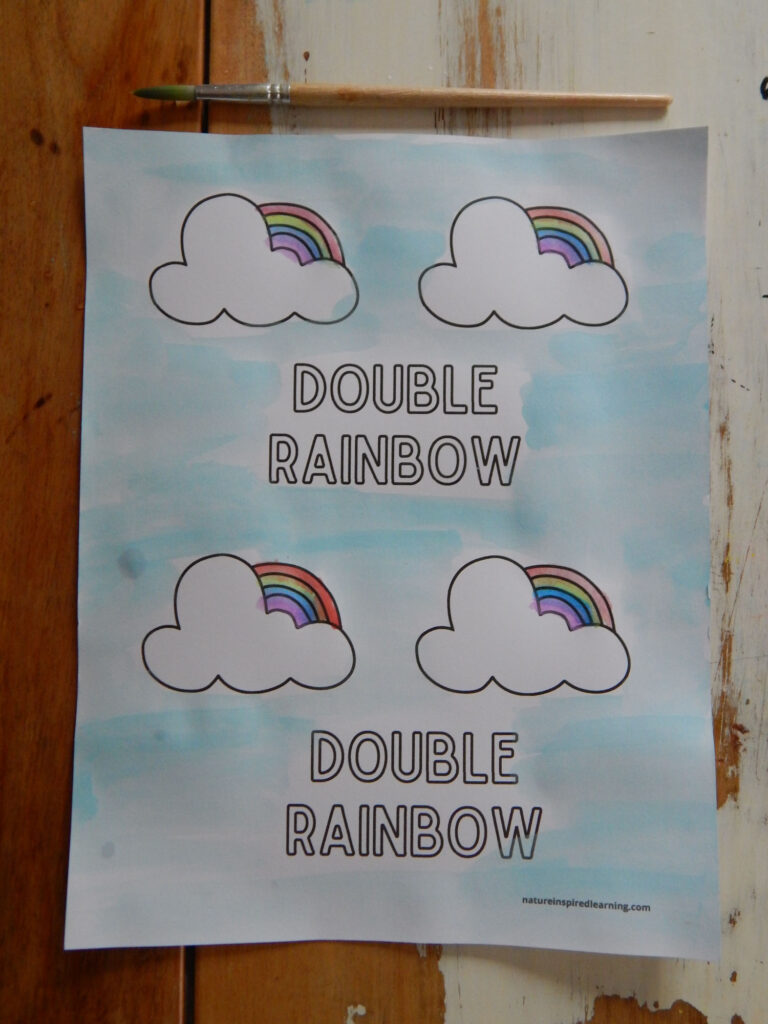 double rainbow coloring page printed off and colored in using rainbow colors with a light blue sky wooden paint brush above printed sheet on wooden table