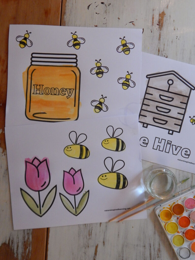 three free bee coloring pages printed off and colored in with paint jar of honey with honey bees, bee hive, and bees with flowers, two paint brushes and watercolor supplies