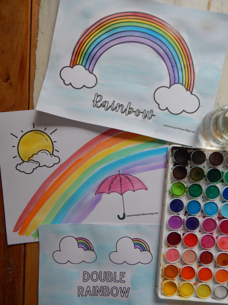 three free printable rainbow coloring pages printed of an placed on a wooden table colored in using watercolor paints in bright rainbow colors roy g biv