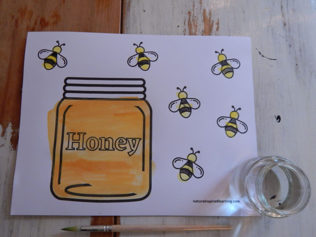 honey bee coloring page printed off on a table jar of honey painted to look like real honey yellow and black stripped bees jar of water and one paint brush