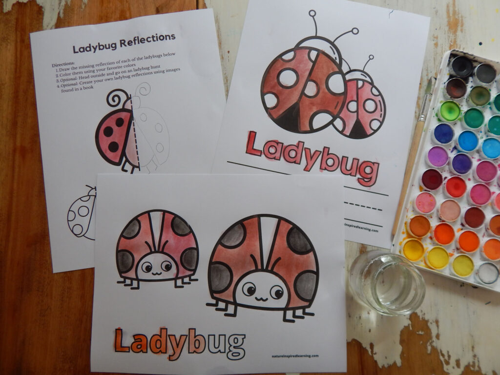 three ladybug coloring pages colored in using red, black, and dark orange paint, paint set, water in a jar, and paint brush on wooden table
