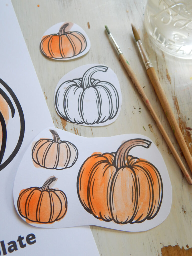 five little pumpkins cut out of a pumpkin coloring page on a pumpkin coloring sheet and wooden table with two paint brushes to the side next to a ball glass with water