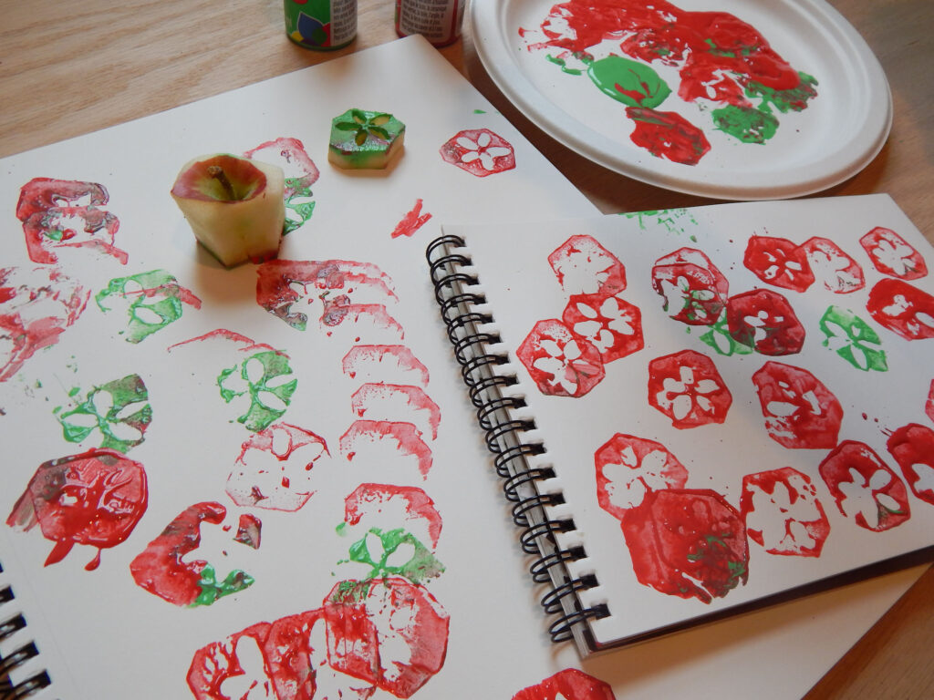 process art made with apple cores on spiral bound blank notebooks with red and green acrylic paint on a paper plate with two apple cores on the paper