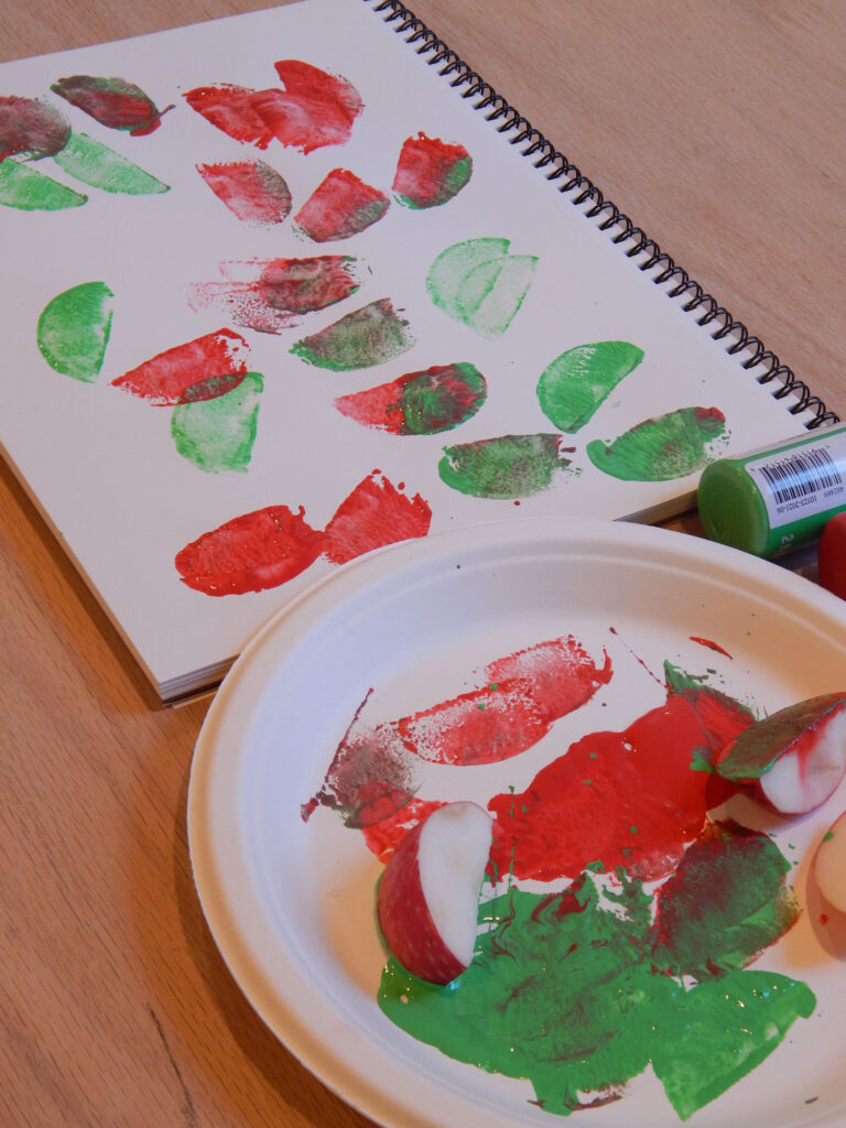 art made with apple slices stamped on blank paper pad with black spiral with green and red acrylic paint on a paper plate with three apple slices and green and red paint bottles
