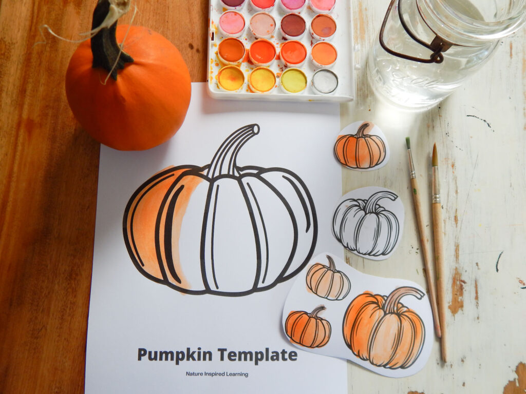 printed off pumpkin template with one large pumpkin partially colored in orange with watercolor paint set above, mini real pumpkin on the sheet with ball glass with water two wooden paint brushes and five paper pumpkins cut out of a coloring sheet four of them painted orange