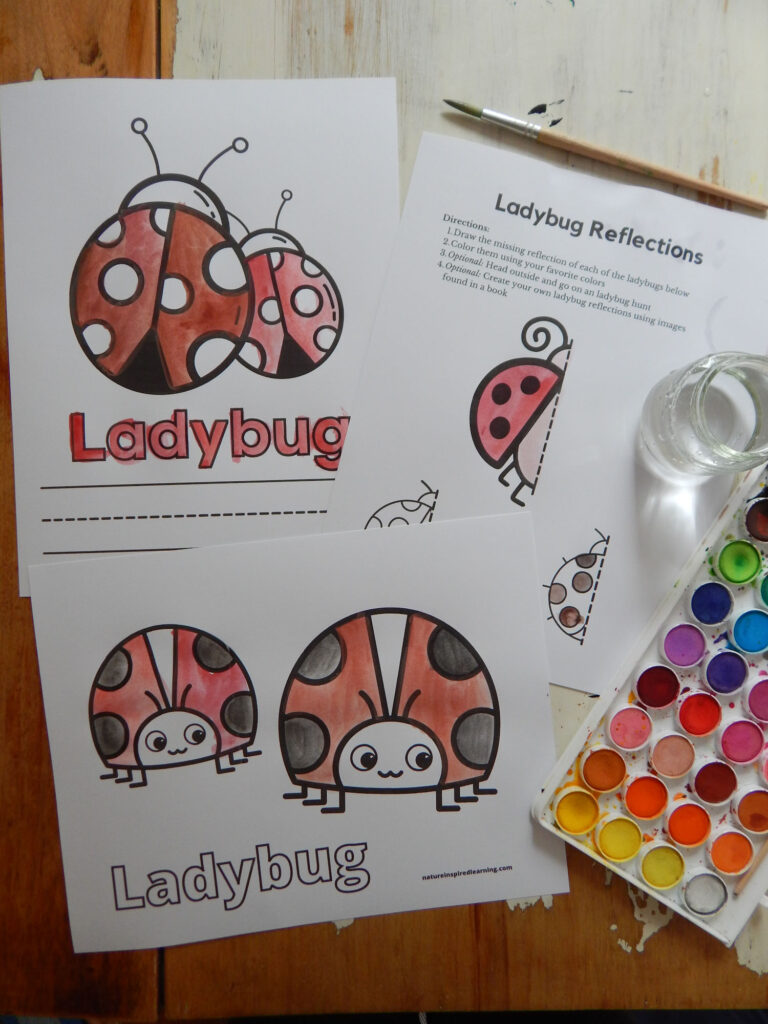 collection of ladybug printables on a table with paint brush, watercolor set, and jar with water. Printables colored in using red and black paint