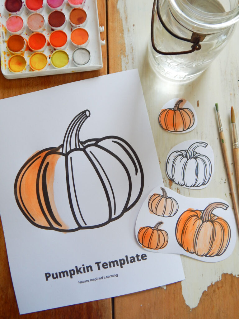 pumpkin coloring page on a wooden table partially colored in orange with watercolor paint set, water, two paint brushes, and five little cut out paper pumpkins