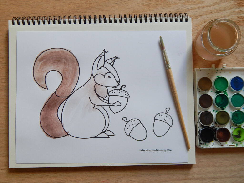 squirrel with an acorn coloring sheet on a blank notepad with watercolor paints, water in a jar, and a wooden paint brush tail of squirrel painted in all on a wooden surface