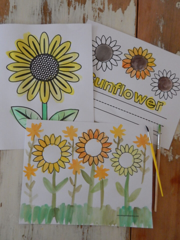 thee free printable sunflower coloring pages on a wooden table painted in using watercolor paints in yellow, green, and brown two paint brushes next to printed sheets