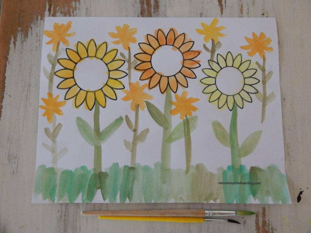 one colored in free sunflower coloring page with two paint brushes under the sheet field of sunflowers printed and hand drawn on the printable