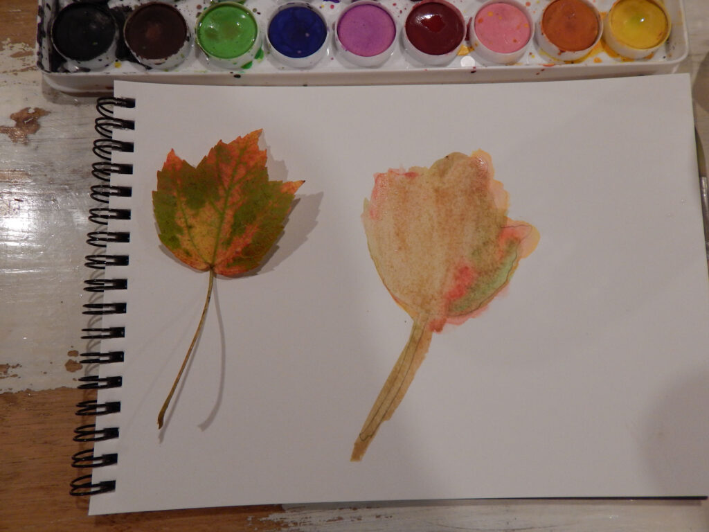 real fall maple leaf with water color maple leaf in progress on a blank note pad with watercolor paint set above all on a wooden table
