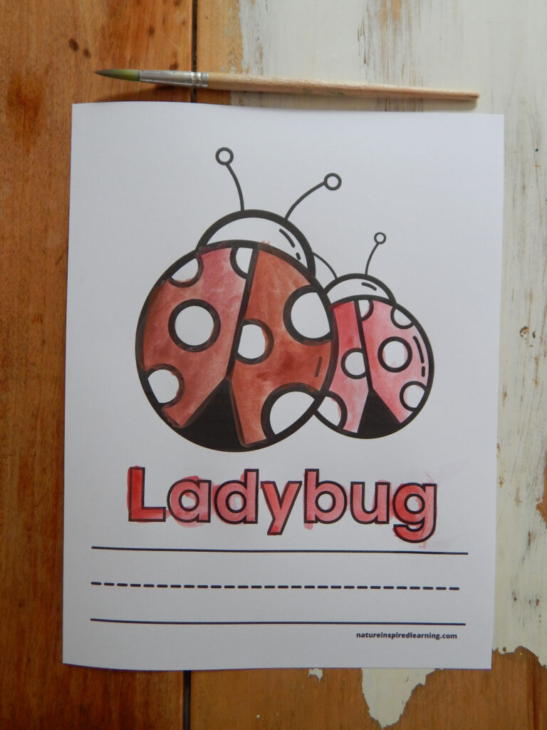 printed off ladybug coloring page with the word ladybug and lines to write the word painted in using red and dark orange paint brush on table above the printable