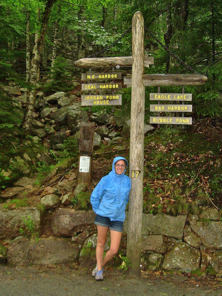 Julie in a blue rain jacket hood up with jean shorts leaning against a wooden hiking sign in the woods in Acadia National Park