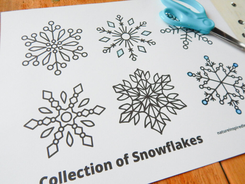 collection of snowflakes coloring page printed off on a table with blue scissors, silver sequins, and light blue colored in some of coloring page on wooden table