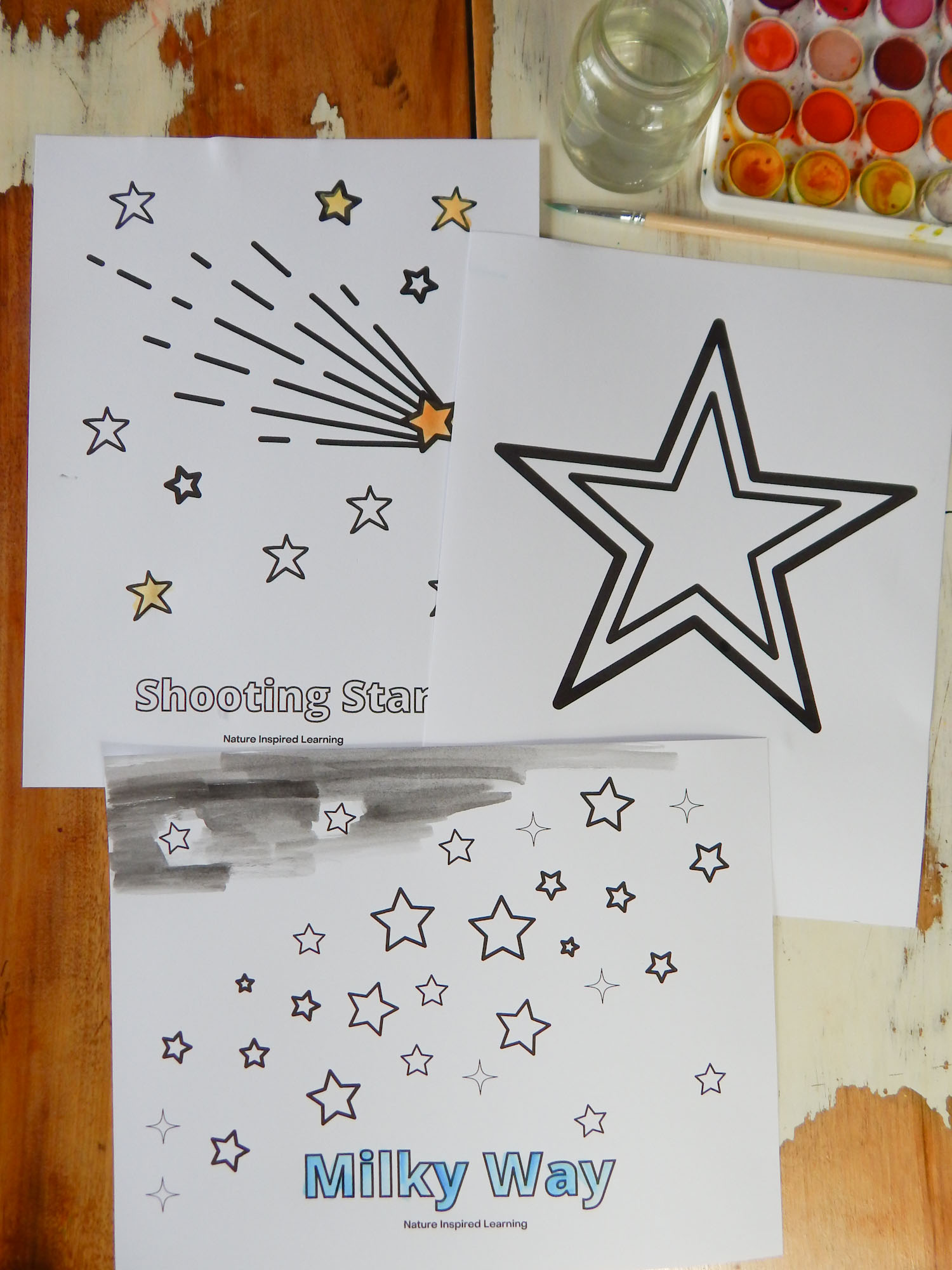 collection of star coloring pages printed out on a wooden table partially colored in using watercolor paint. Large star, milky way, and shooting star sheets. Glass jar with water above, wooden paint brush, and watercolor set top corner