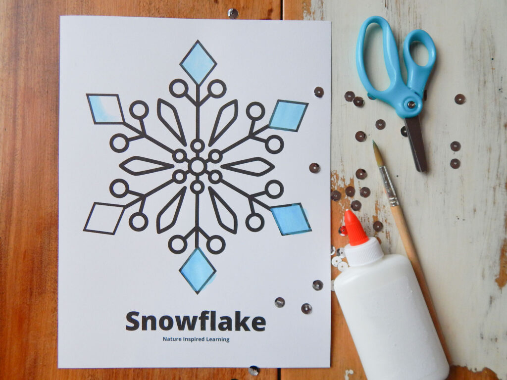 large snowflake coloring page printed off on a wooden table with light blue safety scissors, wooden paint brush, liquid glue, and silver sequins next to the printable