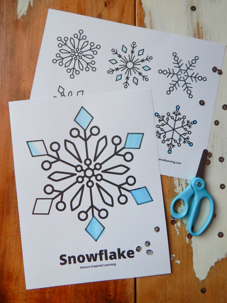 large snowflake coloring page overlapping a small snowflake coloring page both on a wooden table with blue safety scissors to the side with silver sequins